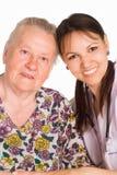 Verpleegster en oude patiënt Royalty-vrije Stock Afbeeldingen