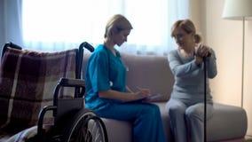 Verpleegster en oude vrouwenzitting op bank bij ziekenhuis, die behandeling, steun het bespreken stock afbeeldingen