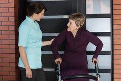 Verpleegster en oudere vrouw die zich voor huis bevinden Royalty-vrije Stock Foto's