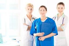 Verpleegster en twee jonge artsen Stock Afbeeldingen
