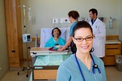 Verpleegster in front van gezondheidsteam stock foto's