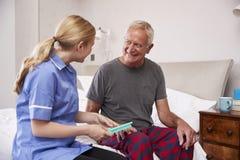 Verpleegster Helping Senior Man om Medicijn op Huisbezoek te organiseren stock afbeeldingen