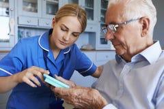 Verpleegster Helping Senior Man om Medicijn op Huisbezoek te organiseren royalty-vrije stock foto's