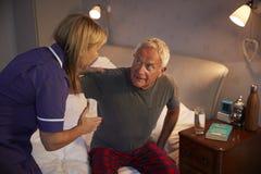 Verpleegster Helping Senior Man uit Bed op Huisbezoek stock foto