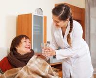 Verpleegster in het eenvormige geven voor gelukkige rijpe vrouw Stock Foto