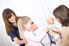 Verpleegster: Het meisje controleert Doll terwijl Verpleegster Checks Girl Royalty-vrije Stock Foto