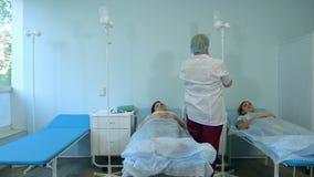 Verpleegster in masker en handschoenen die druppel voor vrouwelijke patiënten in een afdeling voorbereiden stock videobeelden