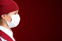 Verpleegster in masker met rode achtergrond stock afbeelding