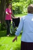 Verpleegster met bejaarde in tuin van pensioneringshuis Stock Foto