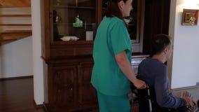 Verpleegster met de jonge mens in rolstoel die naar het terras gaan stock video