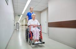 Verpleegster met hogere vrouw in rolstoel bij het ziekenhuis Stock Fotografie
