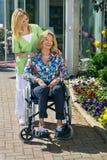 Verpleegster met Hogere Vrouw in Rolstoel in openlucht stock afbeelding
