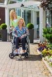 Verpleegster met Hogere Vrouw in Rolstoel in openlucht stock foto's