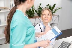 Verpleegster met pen en klembord die glimlachende arts bekijken die laptop met behulp van Stock Foto's
