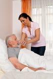 Verpleegster in oude zorg voor de bejaarden in verzorging Royalty-vrije Stock Afbeeldingen