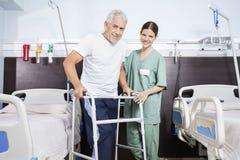 Verpleegster With Senior Man dat Walker In Rehab Center gebruikt Royalty-vrije Stock Afbeeldingen