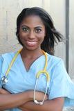 Verpleegster Smiling aan Geïsoleerde het Werk stock afbeelding