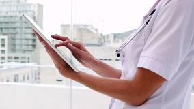 Verpleegster in uniformjas die tabletpc met behulp van stock footage