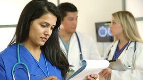 Verpleegster van medisch team die door test kijken resul stock videobeelden