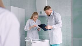 Verpleegster in witte laboratoriumlaag en arts met stethoscoop tellende geneesmiddelen of recepten stock footage
