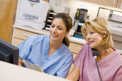 Verpleegsters bij het Gebied van de Ontvangst in het Ziekenhuis stock foto