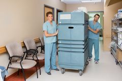 Verpleegsters die Karretje in het Ziekenhuisgang duwen Royalty-vrije Stock Afbeelding