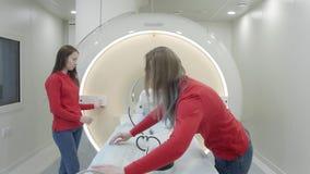 Verpleegsters die magnetic resonance imagingsscanner voorbereiden vóór de patiënt stock videobeelden