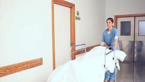 Verpleegsters en arts die een patiënt op zijn bed drijven stock video