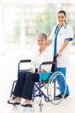 Verpleegsters geduldige rolstoel Stock Afbeeldingen
