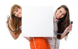 Verpleegsters. Kijk achter lege raad met stethoscoop Royalty-vrije Stock Foto