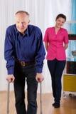 Verpleegstershorloges als gehandicapten die proberen te lopen stock foto