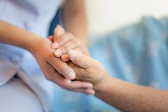 Verpleegsterszitting op een het ziekenhuisbed naast een oudere vrouw die handen, zorg voor het bejaarde concept helpen stock foto's