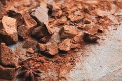 Verpletterde chocoladestukken en cacao op grijze achtergrond Royalty-vrije Stock Afbeelding