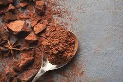 Verpletterde chocoladestukken en cacao op grijze achtergrond Stock Foto's