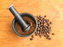 Verpletterde Koffiebonen in een Gietijzermortier Stock Afbeeldingen