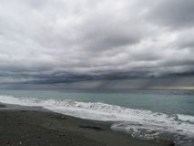 Verpletterende golven op strand met onweerswolken stock fotografie