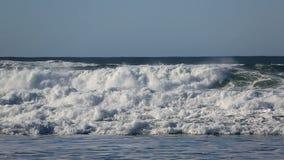 Verpletterende golven over tegen blauwe hemel langs Vreedzame Oceaan in Kanonstrand Oregon stock videobeelden