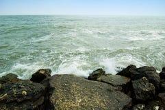 Verpletterende golven tegen rotsen op oever. Royalty-vrije Stock Afbeeldingen