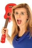 Verrückte blonde Frau mit ihrer offenen Holding des Munds eine Ukulele Lizenzfreie Stockfotografie
