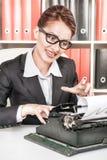 Verrückte Geschäftsfrau, die mit Schreibmaschine arbeitet Stockbild