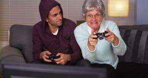 Verrückte Großmutter, die ihren Enkel an den Videospielen schlägt Lizenzfreie Stockfotos