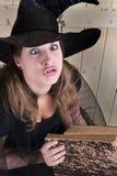 Verrückte Halloween-Hexe mit Buch Stockfoto