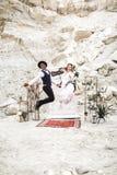 Verr?ckte Hippie springen die multi rationalen Hochzeitspaare, die in boho Art gekleidet werden, vor dem Heiratsbogen in der Schl stockbild