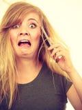 Verrückte junge Frau, die am Telefon spricht Stockfotografie