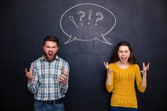 Verrückte Paare, die über Tafelhintergrund schreien Stockfotos