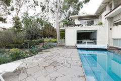 Verrückte Pflasterung neben Swimmingpool im modernen Haus der Mitte des Jahrhunderts lizenzfreie stockfotos