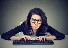 Verrückte schauende Frau, die auf der Tastatur grafisch darstellt eine Rache schreibt Stockbild