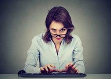 Verrückte schauende nerdy junge Frau, die auf der Tastatur sich wundert was zu antworten schreibt lizenzfreie stockfotos