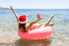 Verrückte Schwimmen mit aufblasbarem Donut- und Weihnachtshut auf dem Strand am sonnigen Tag des Sommers stockfoto