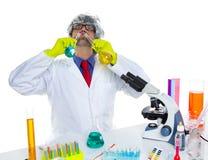 Verrückter dummer Sonderlingswissenschaftler, der chemisches Experiment trinkt Stockbilder